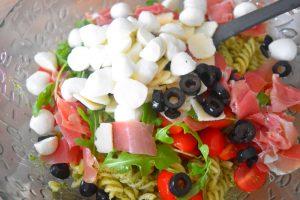 Pâtes, pesto, roquette, tomates, jambon, olives, mozzarella, parmesan